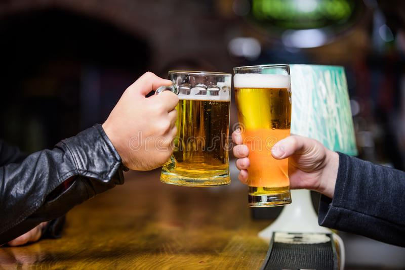Friends cheers glasses. Friday leisure tradition. Beer pub concept. Beer mug on bar counter defocused background. Glass. With fresh lager draft beer with foam royalty free stock photography