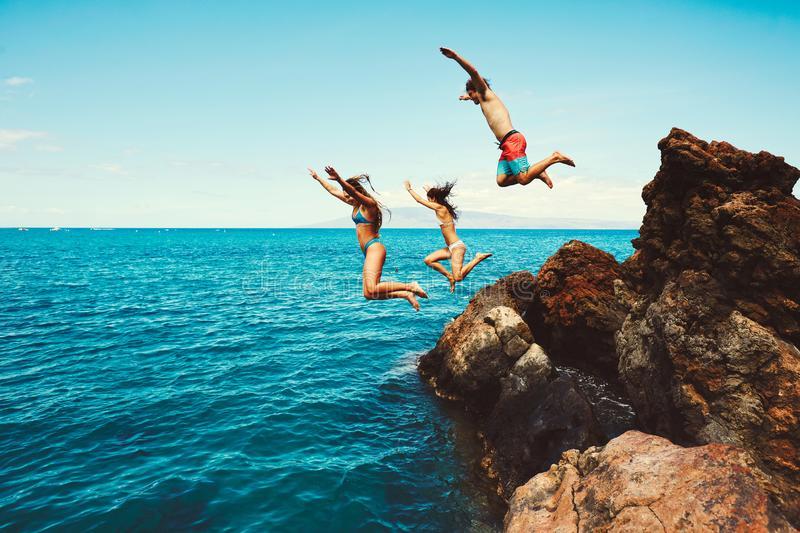 Friends cliff jumping into the ocean stock photography