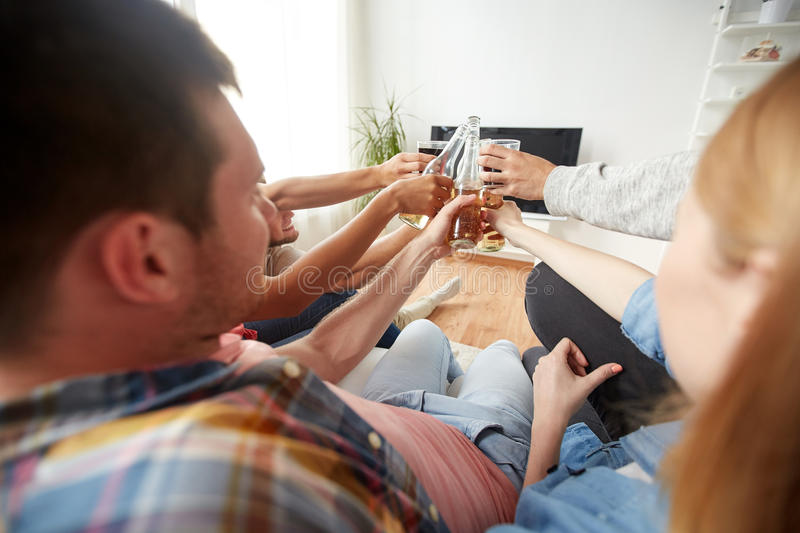 Friends clinking beer and watching tv at home. Friendship, drink, alcohol, holidays and people concept - happy friends clinking beer bottles and watching tv at royalty free stock image