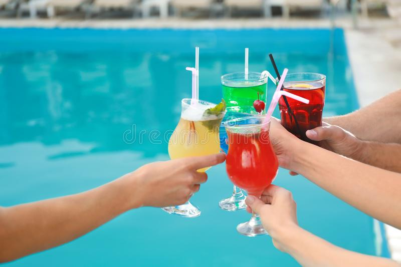 Friends clinking glasses with fresh summer  near swimming pool, closeup stock photo