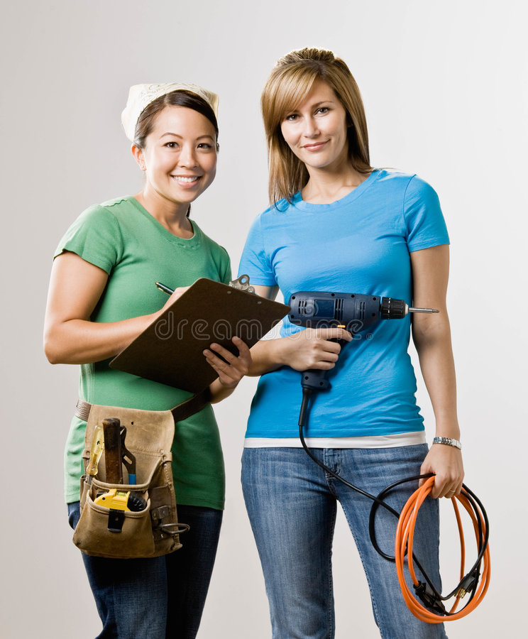 Friends with clipboard, drill and tool belt. Self-sufficient friends with clipboard, drill and tool belt stock photos