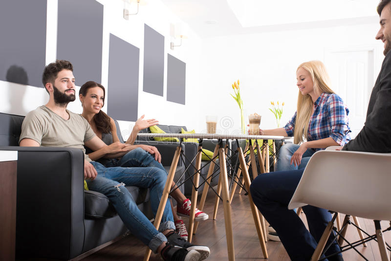 Friends in a coffee shop. Friends siting and talking at a table in a coffee shop royalty free stock image