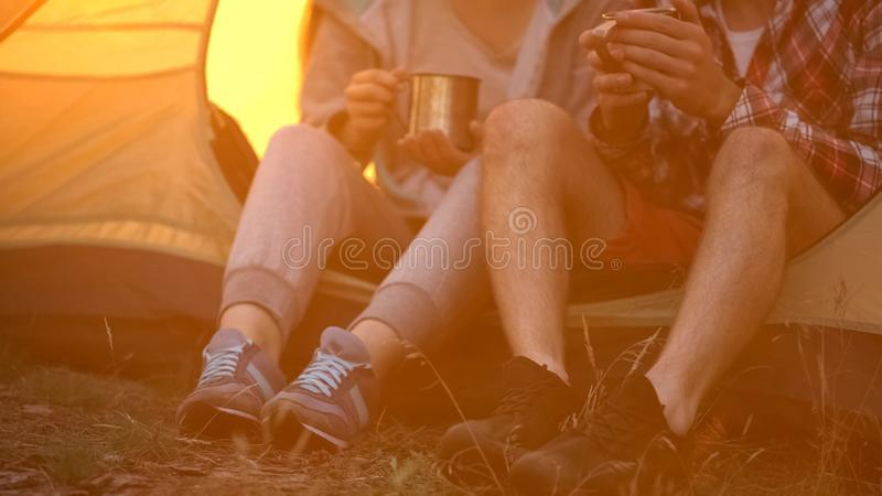 Friends in comfortable shoes sitting in tent and drinking tea, hiking in forest stock photo