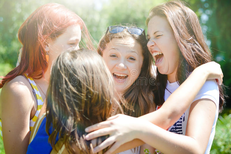 Friends congratulating a girl on her birthday. Four happy female friends hugging in green summer park sun light outdoors background royalty free stock photography