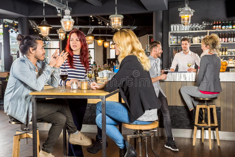 Friends Conversing While Sitting At Table In Bar. Young friends conversing while sitting at table in bar stock images