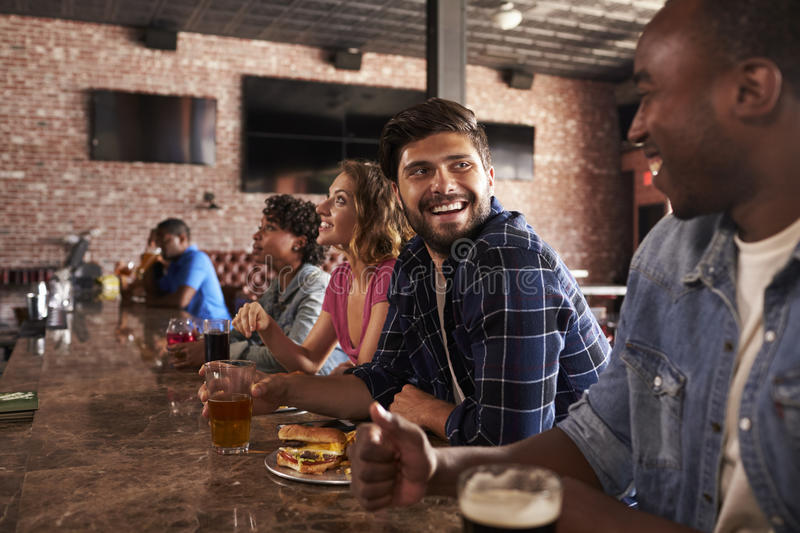 Friends At Counter In Sports Bar Watching Game stock images