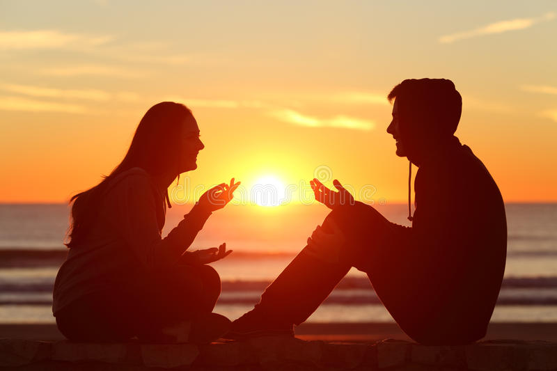 Friends or couple of teens talking at sunset royalty free stock images