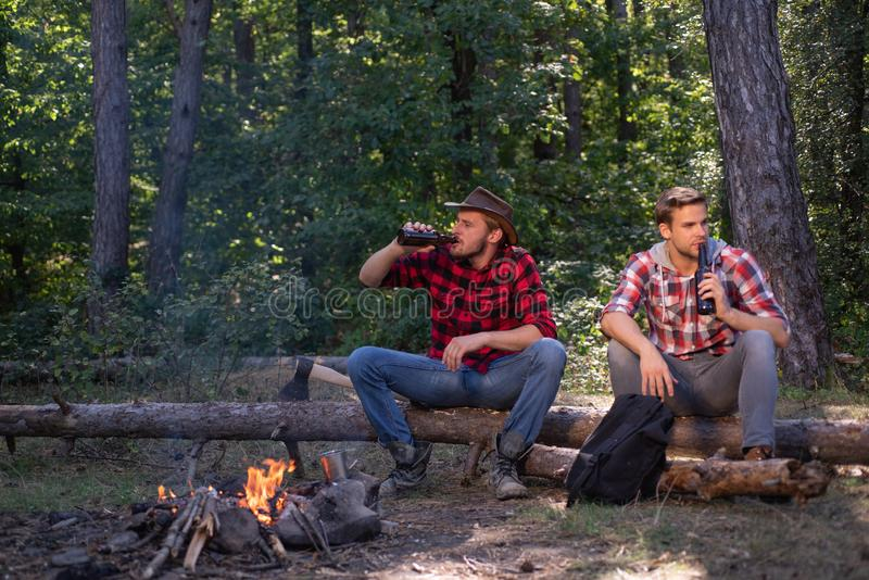 Friends couples enjoy vacation or weekend forest. Happy friends on a camping trip relaxing by campfire. Company two male stock photography