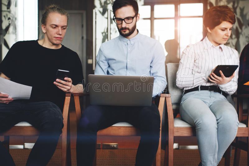Friends of coworkers working together for modern gadgets, smartphone, laptop, tablet in loft office. Friendship creative . stock image