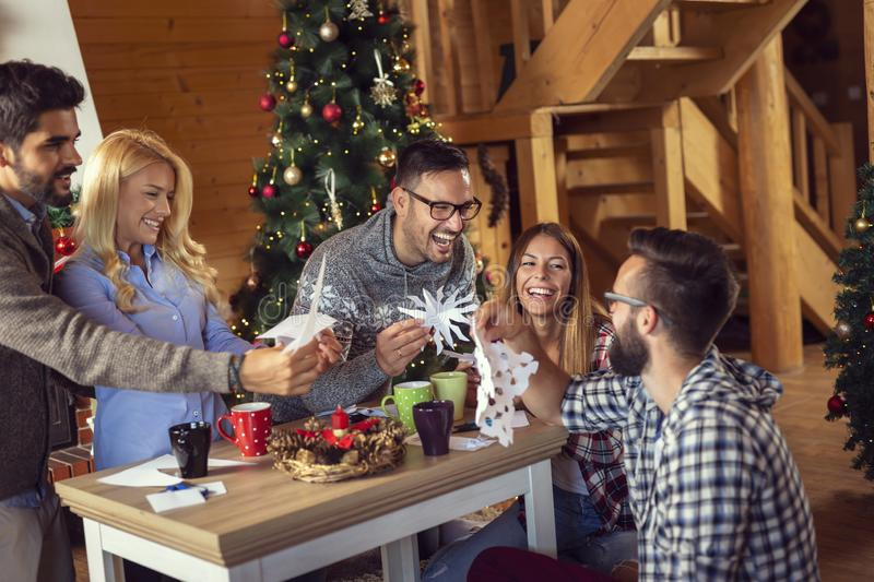 Friends cutting paper snowflakes royalty free stock images