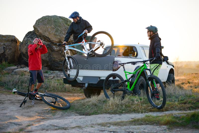 Friends Taking MTB Bikes off the Pickup Offroad Truck in Mountains at Sunset. Adventure and Travel Concept. Friends Cyclists Getting Ready for Bike Riding and royalty free stock images