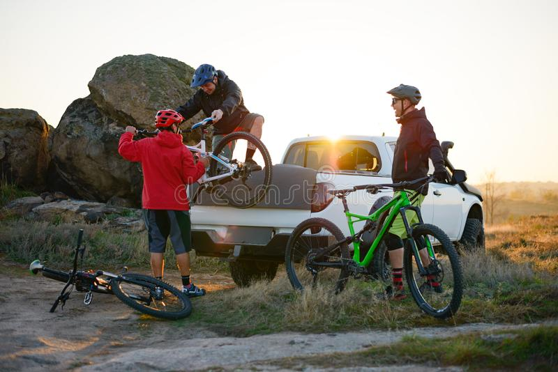 Friends Taking MTB Bikes off the Pickup Offroad Truck in Mountains at Sunset. Adventure and Travel Concept. Friends Cyclists Getting Ready for Bike Riding and stock photo