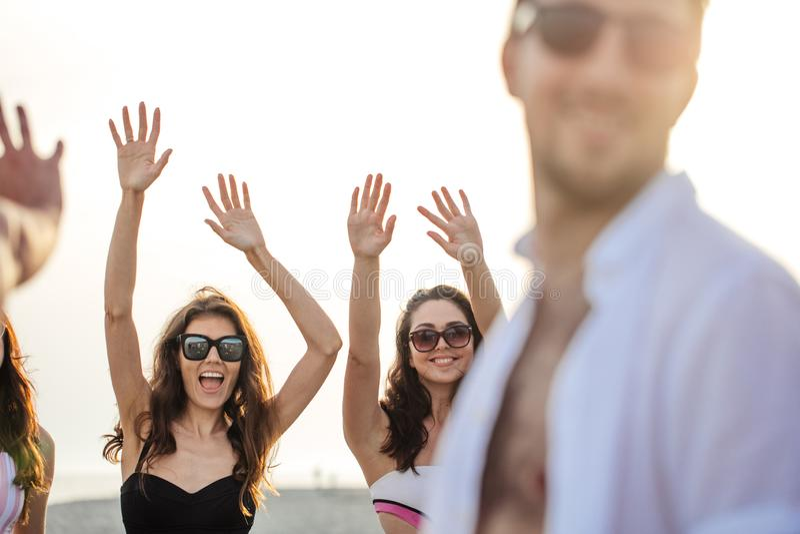 Friends dance on beach under sunset sunlight, having fun, happy, enjoy royalty free stock photography