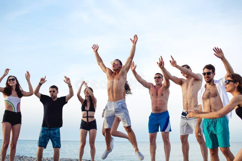 Friends dance on beach under sunset sunlight, having fun, happy, enjoy. Group of Friends Having Party on Beach, dance, jump and fun stock image
