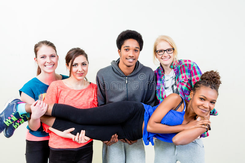 Friends in dance class carrying woman on hands. Friends in dance class carrying women on hands stock photo