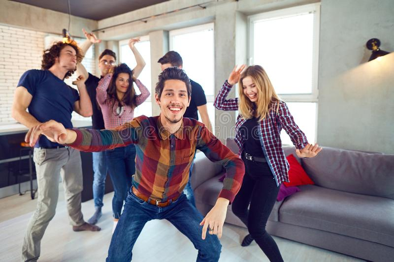 Friends dance fun at a student`s party in the apartment.  stock images