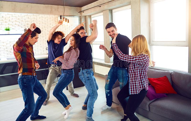 Friends dance at a student`s party in the apartment. Friends dance fun at a student`s party in the apartment stock photos