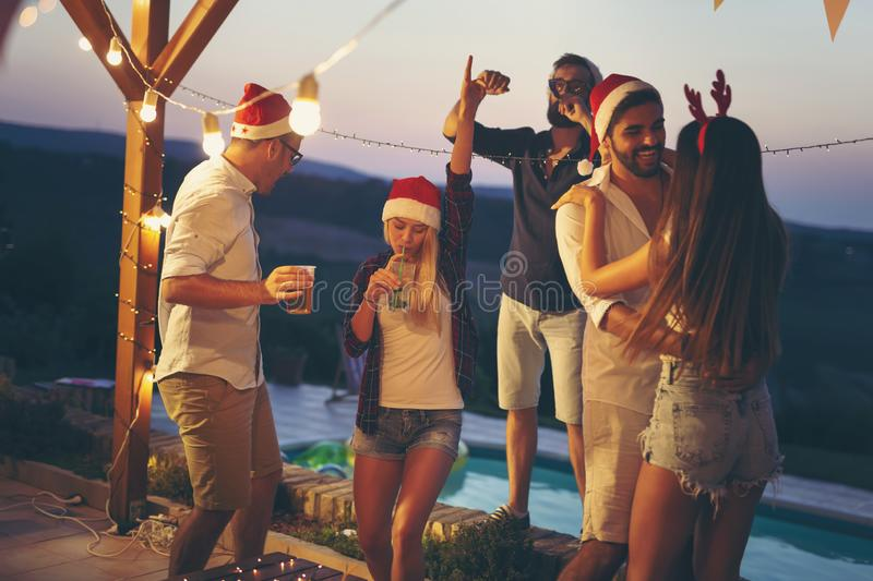 Friends dancing at poolside New Year`s party stock image