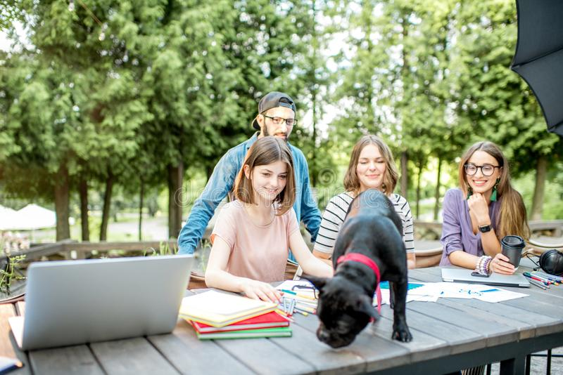Friends with dog during a study outdoors. Friends having fun together sitting with dog during a study outdoors at the park cafe stock images