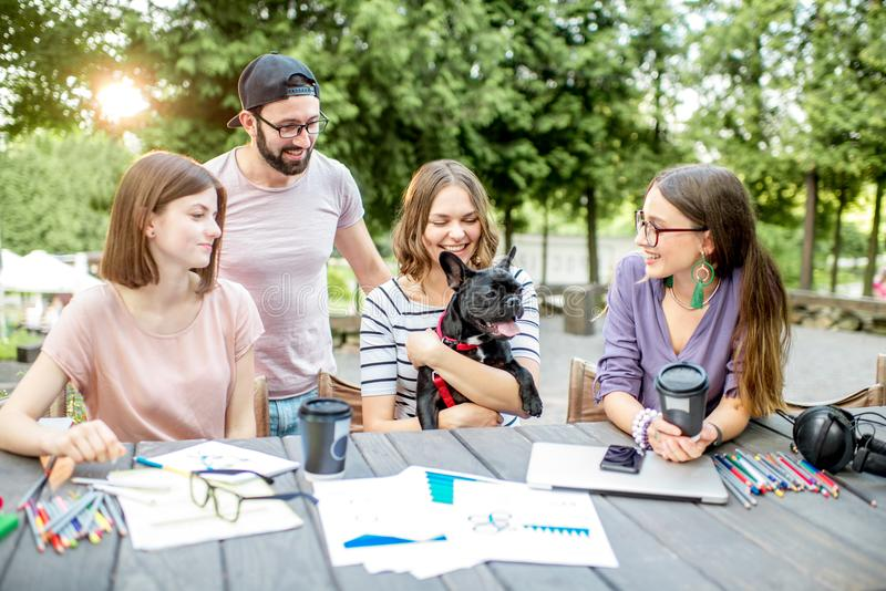 Friends with dog during a study outdoors. Friends having fun together sitting with dog during a study outdoors at the park cafe royalty free stock photo