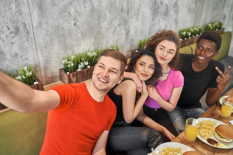 Friends doing selfie, sitting together in cafe. stock photography