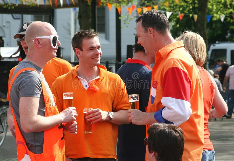 Dutch friends with orange suits and a beer, Koningsdag (Kingsday),Holland. Friends are dressed up in the national Dutch colors orange, red, white and blue with a royalty free stock image