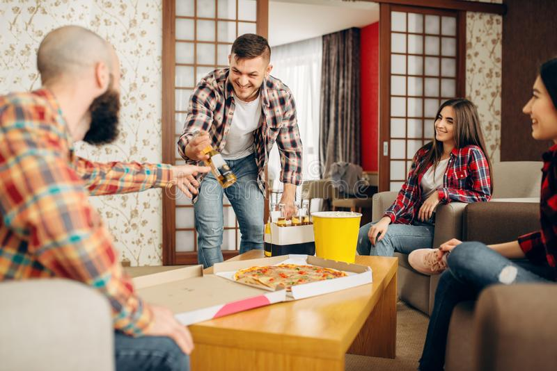 Friends drink a beer with pizza at the home party. Smiling friends going to drink a beer with pizza at the home party. Good friendship, group of people leisures stock photo