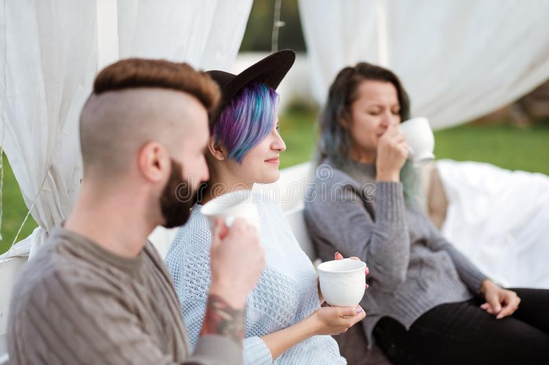 Friends drink tea and have a good time on the terrace of a country house. stock photography