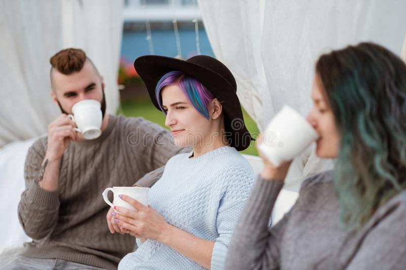 Friends drink tea and have a good time on the terrace of a country house. stock images