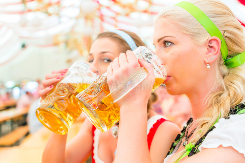 Friends drinking Bavarian beer at Oktoberfest. Women drinking Bavarian beer in tent on Oktoberfest or dult wearing dirndl royalty free stock images