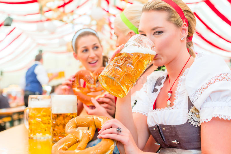 Friends drinking Bavarian beer at Oktoberfest. Women drinking Bavarian beer in tent on Oktoberfest or dult wearing dirndl royalty free stock photo