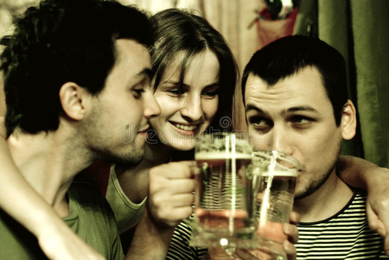 Friends drinking beer. A young adult woman and two guys drinking beer together. Fraternizing. Smiling and enjoying themselves while drinking. Image has some stock image