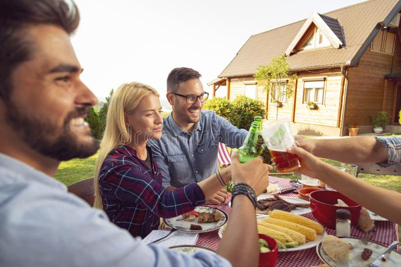 Friends drinking beer at barbeue party. Group of young friends having an outdoor barbecue lunch, making a toast while sitting at the table, drinking beer and stock images