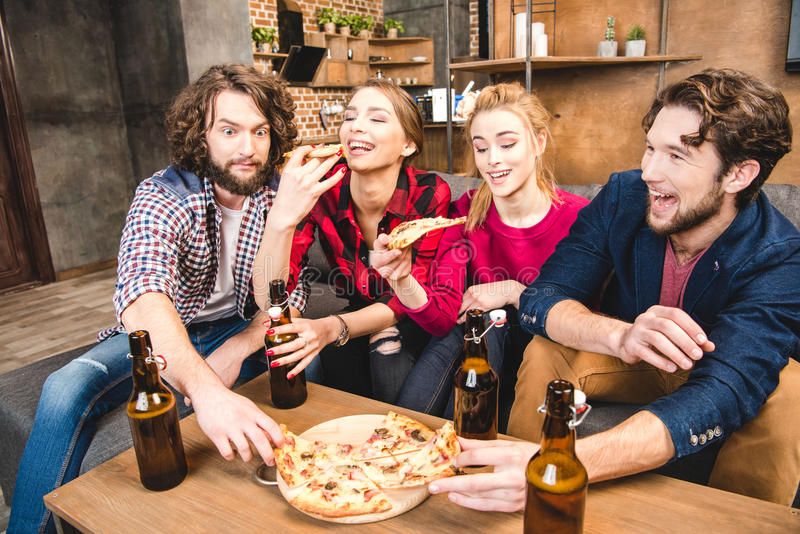 Friends drinking beer and eating pizza. Smiling friends drinking beer and eating pizza while sitting on sofa stock photos