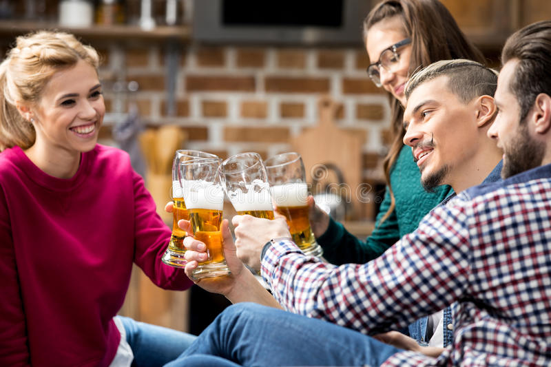 Friends drinking beer. Happy young friends drinking beer and clinking glasses stock image