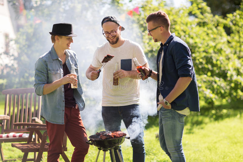 Friends drinking beer at summer barbecue party. Leisure, food, people, friendship and holidays concept - happy friends cooking meat on barbecue grill and stock photos