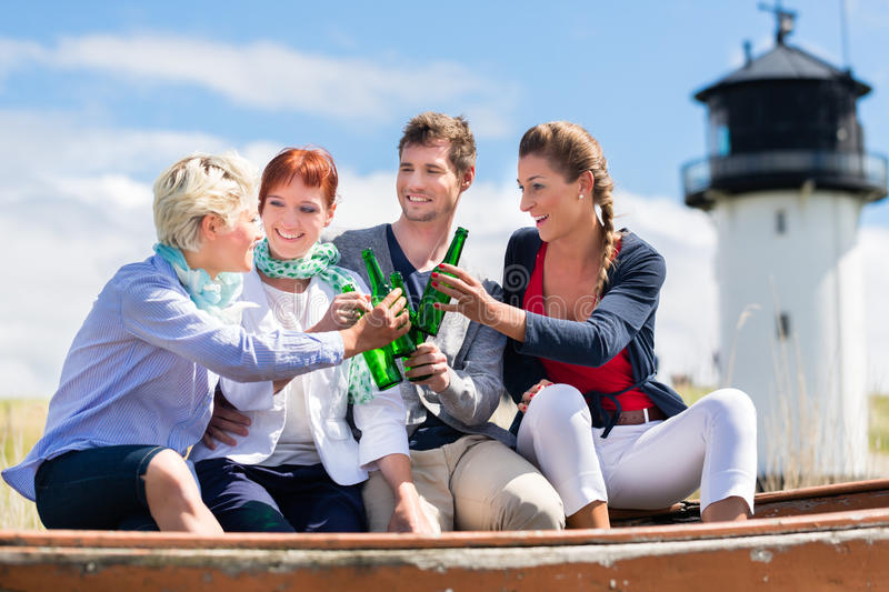 Friends drinking bottled beer at beach royalty free stock photography
