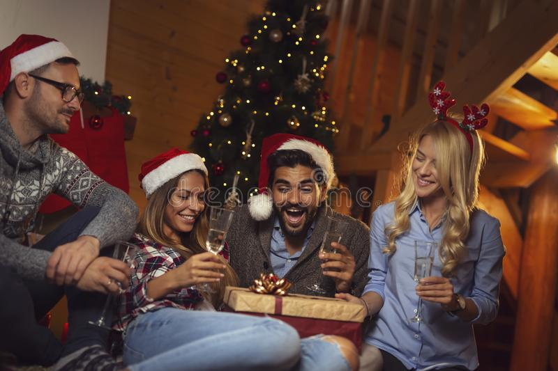 Friends drinking champagne and opening presents on Christmas Eve royalty free stock image