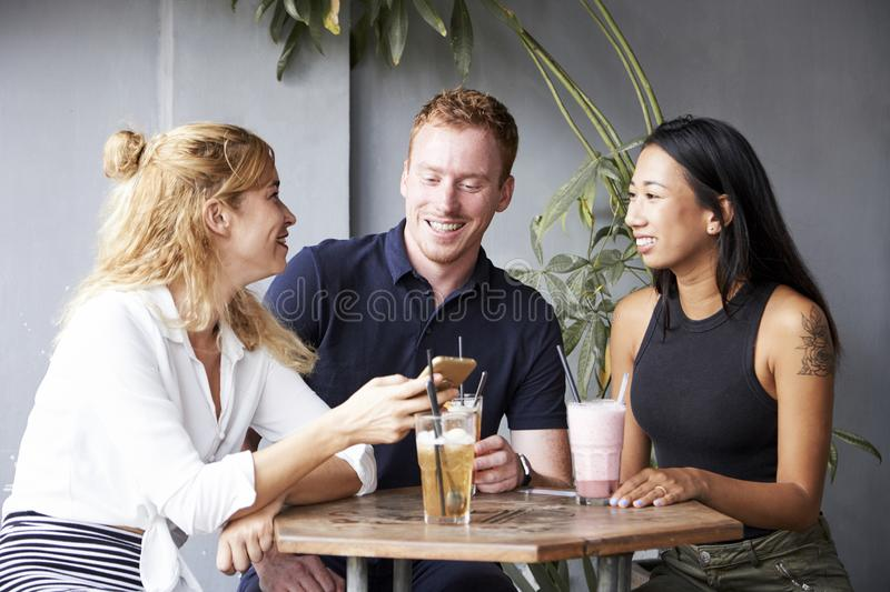 Friends drinking cocktails in cafe stock images