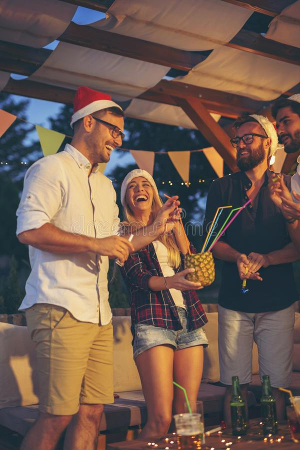 Friends drinking cocktails at New Year party stock image