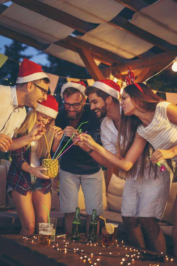 Friends drinking pineapple cocktail at New Year party royalty free stock image