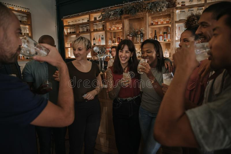 Friends drinking and talking together in a bar at night stock image