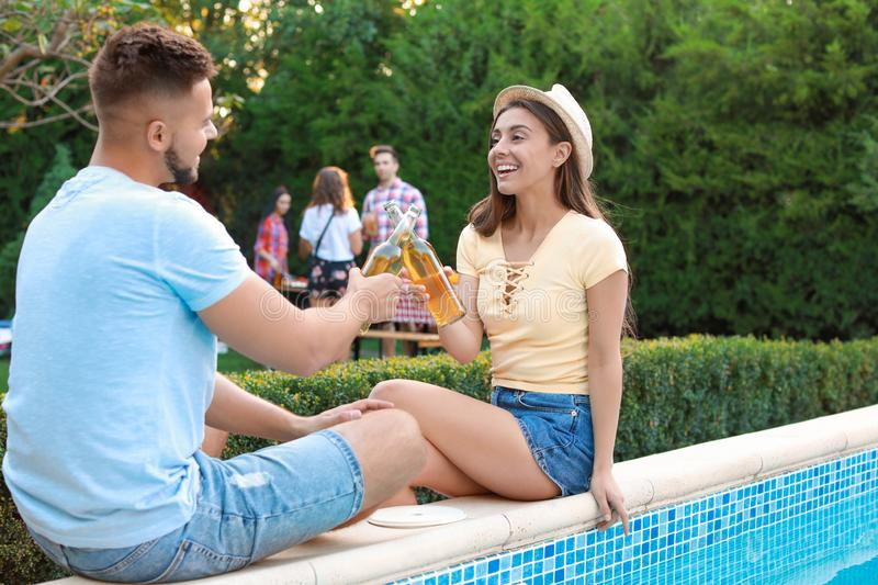 Friends with drinks at barbecue party near swimming pool royalty free stock images