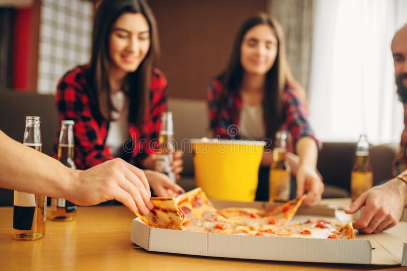 Friends drinks beer with pizza at the house party. Smiling friends drinks beer with pizza at the house party. Good friendship, group of people leisures together royalty free stock photo