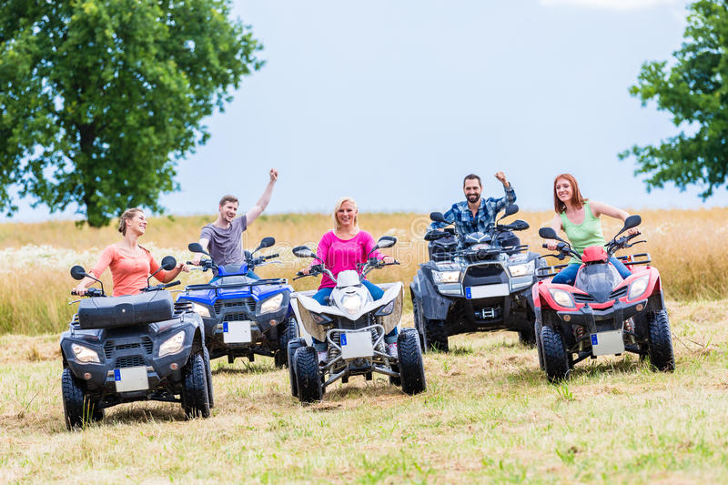 Friends driving off-road with quad bike. Or ATV stock photo