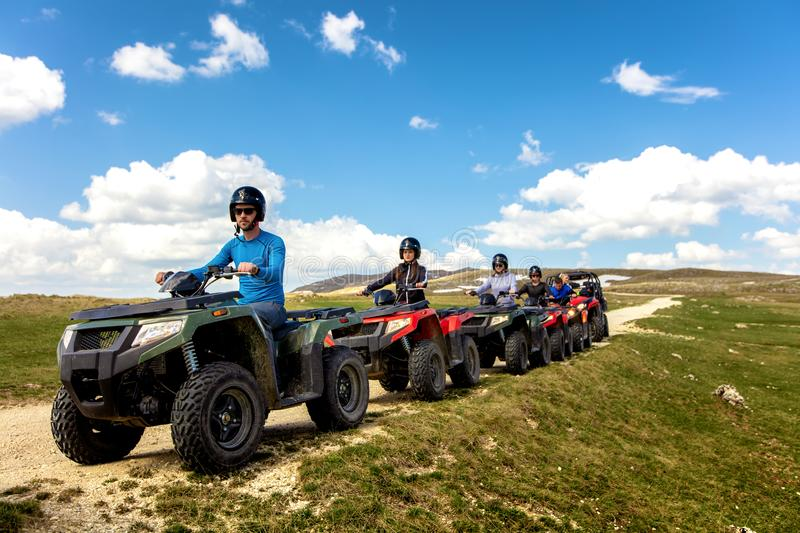 Friends driving off-road with quad bike or ATV and UTV vehicles.  royalty free stock images