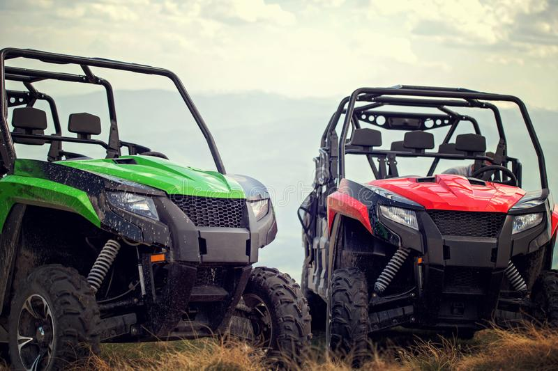 Friends driving off-road with quad bike or ATV and UTV vehicles.  stock photo