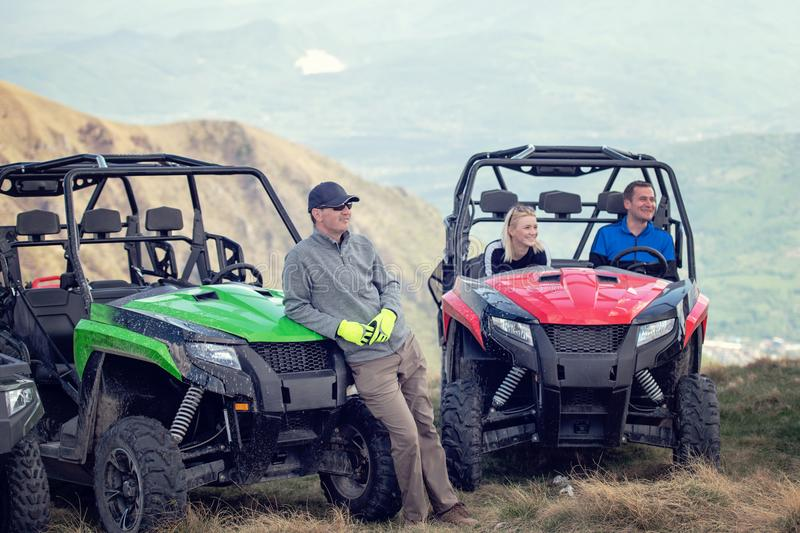 Friends driving off-road with quad bike or ATV and UTV vehicles.  stock images