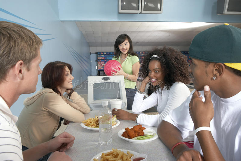 Friends Eating At Bowling Alley. Group of multiethnic friends eating at bowling alley stock images
