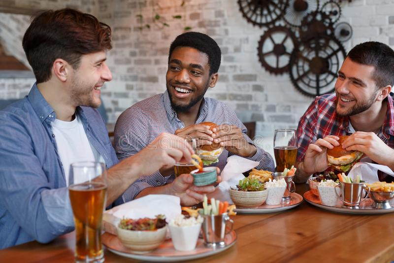 Friends Eating Burgers And Enjoying Beer, Sitting In Bar stock image